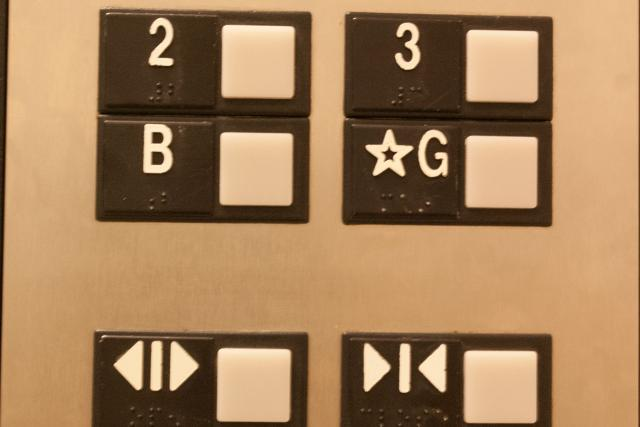 "Photograph of elevator buttons found in the Lassounde building at York University. The embossed type on button for the ground floor (upper right) says ☆G but the braille says ""main""."